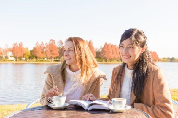 池のほとりでお茶する二人の女性