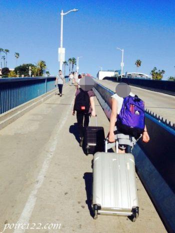 サンタモニカでスーツケースをガラガラ引いている後ろ姿